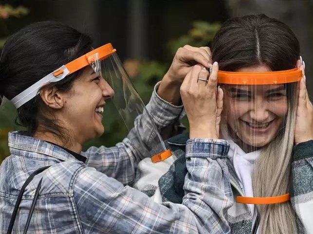 Mulheres usando protetor facial
